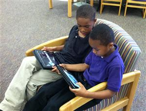 boys reading ipad